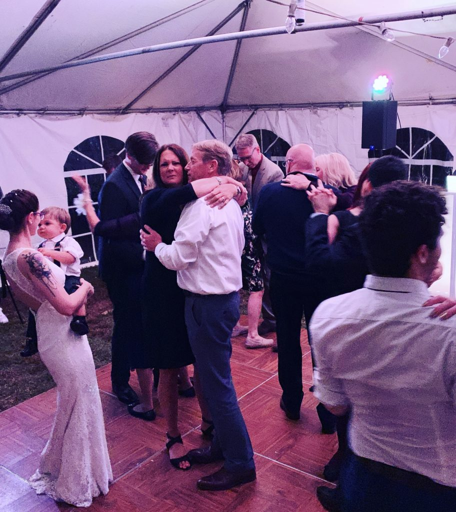 Bride slow dancing at a wedding with a baby